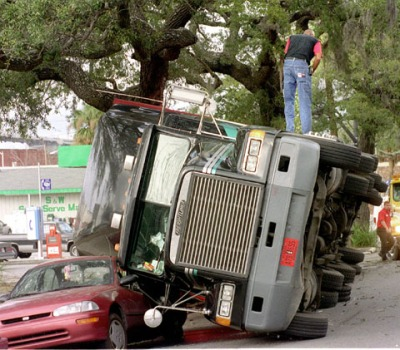 David James, a driver for Great Point Intermodel of Jacksonville, Fla., climbs out of his rig on MLK Jr., Blvd near Bay Street. The truck, carrying 41,000 lbs. of ferric choloride, overturned when the load shifted. Bob Morris photo.